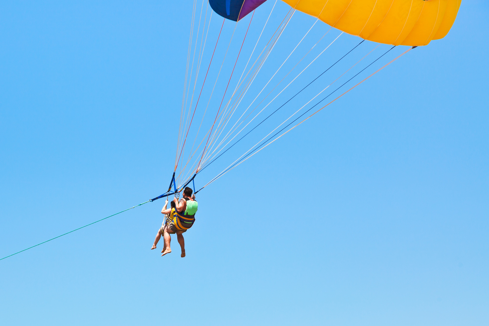 couple people parasailing on parachute in blue sky